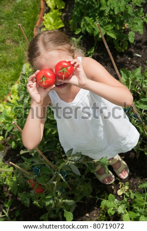 Vegetable garden - funny girl with fresh tomatoes - stock photo