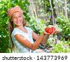 Vegetable garden - portrait of little gardener girl with organic zucchini and tomatoes - stock photo