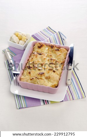 Vegetable gratin with cheese cauliflower in pink plate on a white plate striped napkin - stock photo