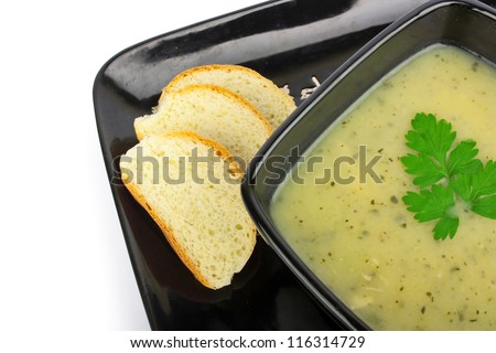 Vegetable green cream soup in black bowl, food photo