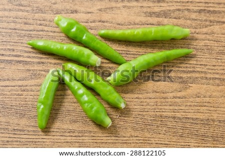 Vegetable, Green Hot Chili or Chilli Cayenne Pepper on A Brown Wooden Table - stock photo
