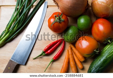 Vegetable ingredient on wood cut board with knife. - stock photo