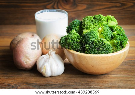 Vegetable ingredients for broccoli soup on wooden background. - stock photo