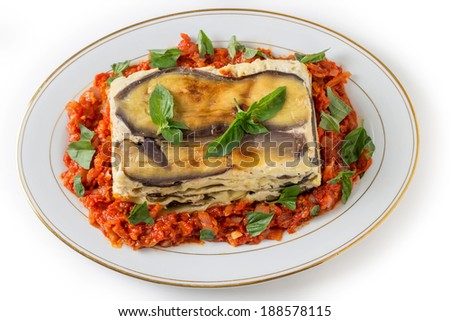 Vegetable lasagne, made with courgettes and eggplants (zucchini and aubergines), pasta sheets and bechamel sauce, served with a tomato and onion sauce and a basil garnish,high angle - stock photo