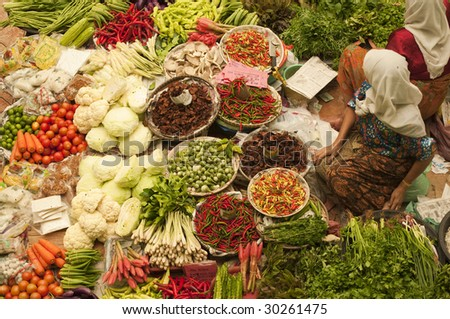 Vegetable market. Muslim woman selling fresh vegetables at market in Kota Bharu Malaysia. - stock photo
