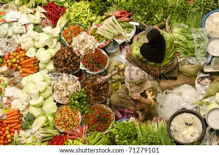 Vegetable market. Muslim woman selling fresh vegetables at Siti Khadijah Market market in Kota Bharu Malaysia. - stock photo