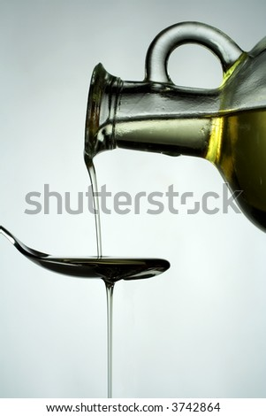 Vegetable oil being poured from a carafe onto a spoon.  Isolated on white background. - stock photo