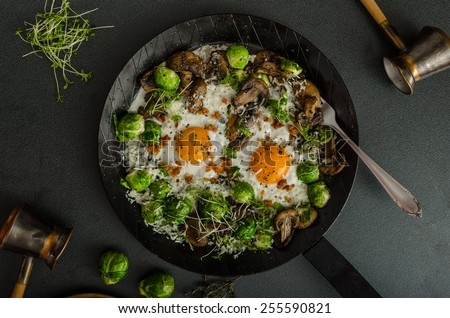 Vegetable omelet with bulls eye fried egg, mushrooms and Brussels sprouts - stock photo