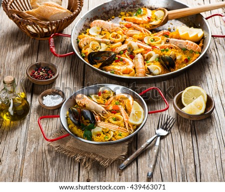 Vegetable paella with seafood on a rustic wooden table.