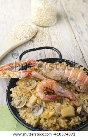 Vegetable paella with seafood on a wooden background - stock photo