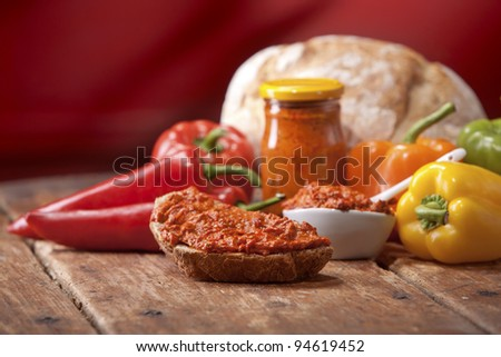 Vegetable Pepper Spread on bread, on wooden table, red background - stock photo