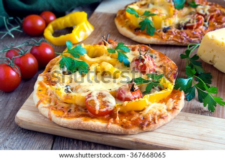 Vegetable pizza and ingredients on wooden cutting board