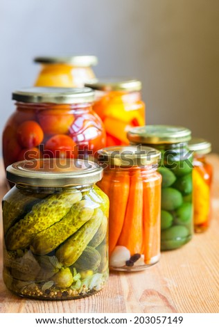 Vegetable preserves on wooden table - stock photo
