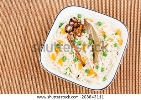 Vegetable Pulao - Closeup view from the top of delicious vegetable pulao garnished with bay leaf, cinnamon stick and fried onion. - stock photo