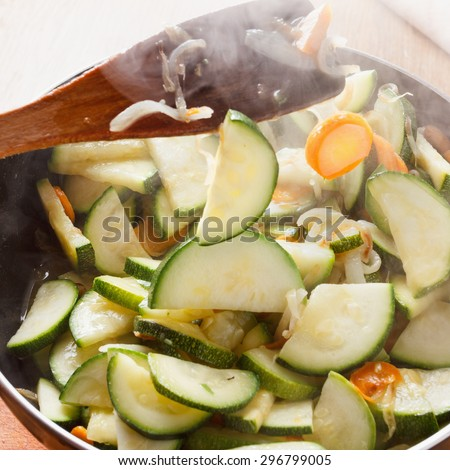 Vegetable ragout. Zucchini and onions with carrots in a pan. steam rises up. - stock photo