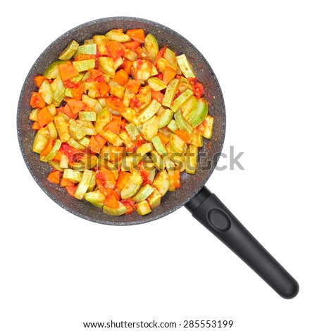 Vegetable ragout. Zucchini and tomatoes with carrots in a pan. - stock photo