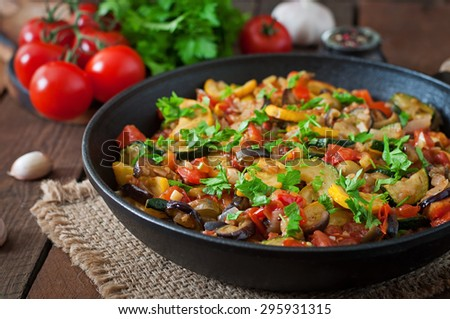 Vegetable Ratatouille in frying pan on a wooden table - stock photo