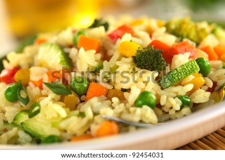 Vegetable risotto made of zucchini, pea, carrot, red bell pepper, broccoli and pumpkin (Selective Focus, Focus in the middle of the image) - stock photo