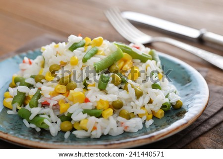 Vegetable risotto on plate with fork and knife on wooden background