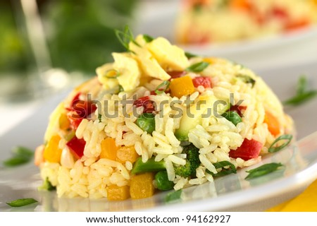 Vegetable risotto with scrambled egg on top garnished with shallot (Selective Focus, Focus on the front of the risotto pile) - stock photo