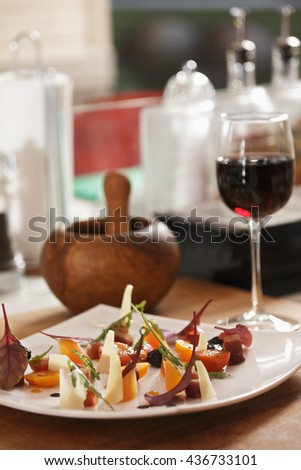Vegetable salad and glass of red wine on a kitchen table closeup