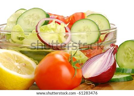 Vegetable salad bowl and salad ingredients on breadboard - stock photo