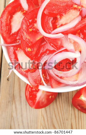 vegetable salad : fresh tomato salad with onion in white bowl over wood