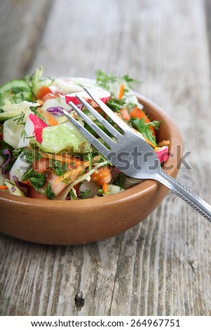 Vegetable salad in a wooden bowl on a wooden table - stock photo
