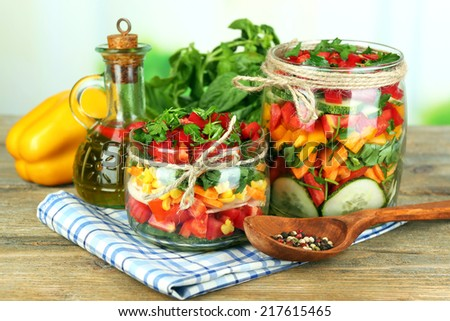 Vegetable salad in glass jars on wooden table, on bright background - stock photo