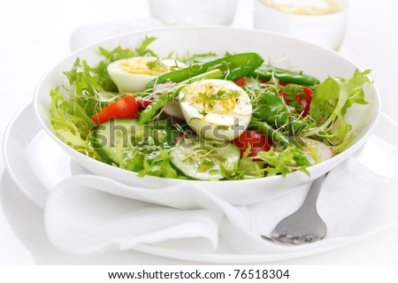 Vegetable salad of tomatoes, cucumbers, asparagus and young green peas - stock photo