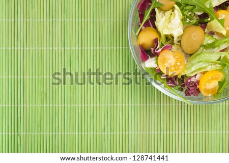 Vegetable salad on green background top view