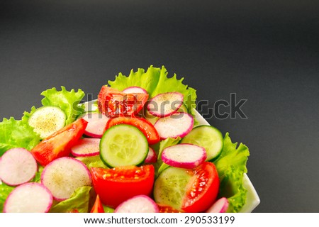 vegetable salad on white plate on dark background