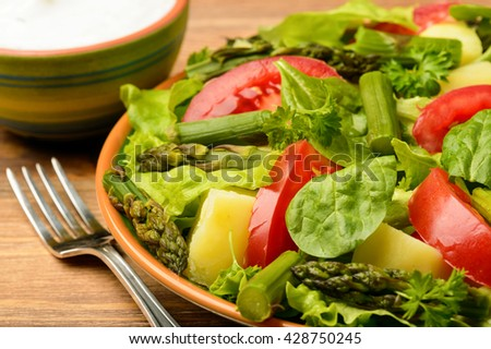 Vegetable salad with asparagus, young potatoes, lettuce, tomatoes and spinach, served with garlic sauce.