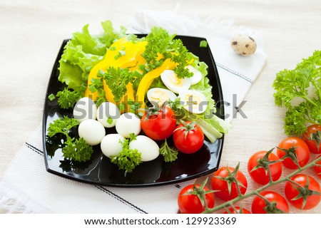 vegetable salad with boiled quail eggs, closeup