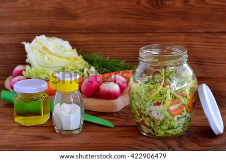 Vegetable salad with chopped cabbage, carrots, radish, dill, olive oil. Vegetarian food. Healthy eating. Fresh vegetables on a cutting board. Delicious and vitamin meals - stock photo