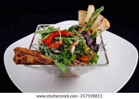 Vegetable salad with toasted black and white bread, pepper, herbs, onions, lettuce, decorated with drops of brown sauce, served in a glass salad bowl on a white plate - stock photo