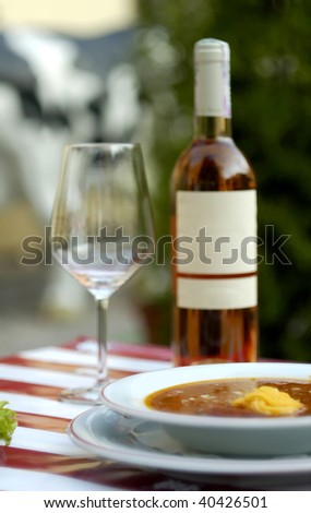 Vegetable soup and expensive wine at restaurant (shallow dof) - stock photo