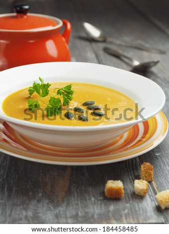 Vegetable soup decorated parsley and pumpkin seeds - stock photo