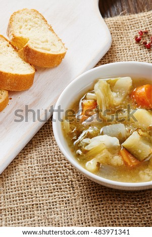 Vegetable soup in white bowl on dark wood table