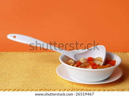 vegetable soup in white bowl, yellow tablecloth and orange background
