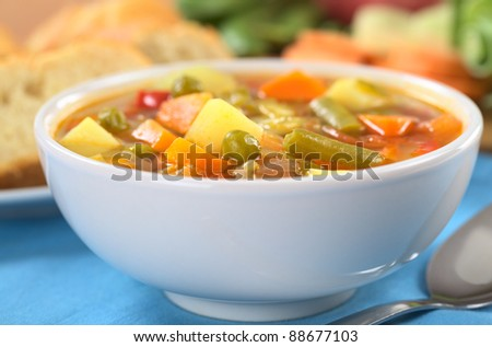 Vegetable soup made of green bean, pea, carrot, potato, red bell pepper, tomato and leek in white bowl (Selective Focus, Focus on the vegetables one third into the soup) - stock photo