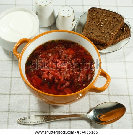 Vegetable soup.  Traditional Ukrainian soup with fresh vegetables with sour cream. Rye bread, salt and spoon,. Serving on a white tablecloth. - stock photo