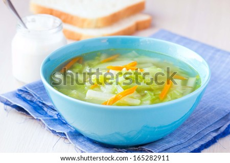Vegetable soup with cabbage, kohlrabi, carrots, healthy vegetarian diet dish with sour cream and bread - stock photo