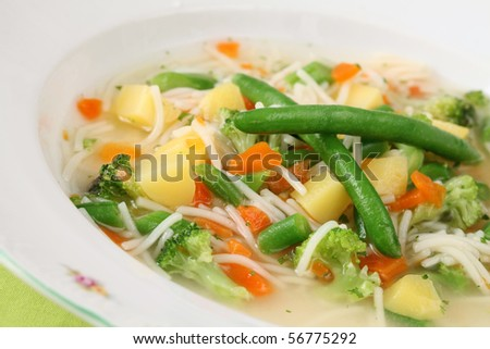Vegetable soup with carrot, potato, broccoli, green beans, parsley and noodles - stock photo