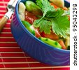 vegetable, vegetarian salad (cucumbers, tomatoes, parsley) in deep blue plate on the pink, bamboo towels - stock photo