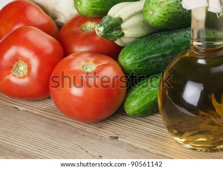 vegetables and a bottle of oil, still life on a wooden table - stock photo