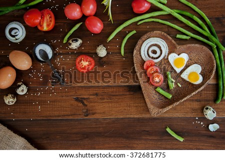 Vegetables and a plate with fried eggs in heart shape on wooden background overhead close up shoot - stock photo