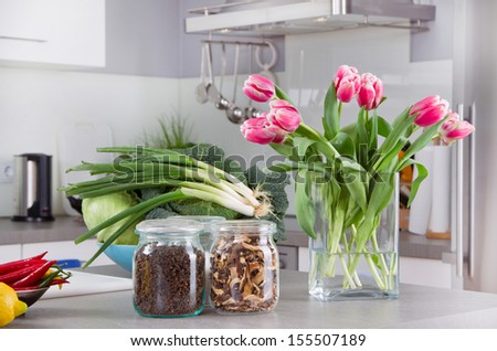 Vegetables and flowers on kitchen counter - stock photo