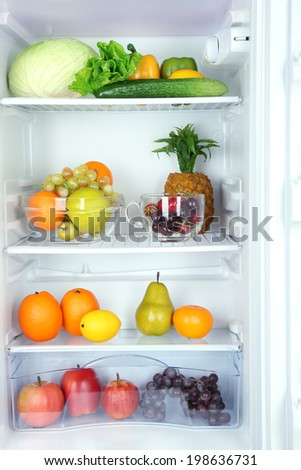 Vegetables and fruits in open refrigerator. Weight loss diet concept. - stock photo