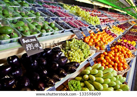 Vegetables and fruits on shelfes in supermarket - stock photo